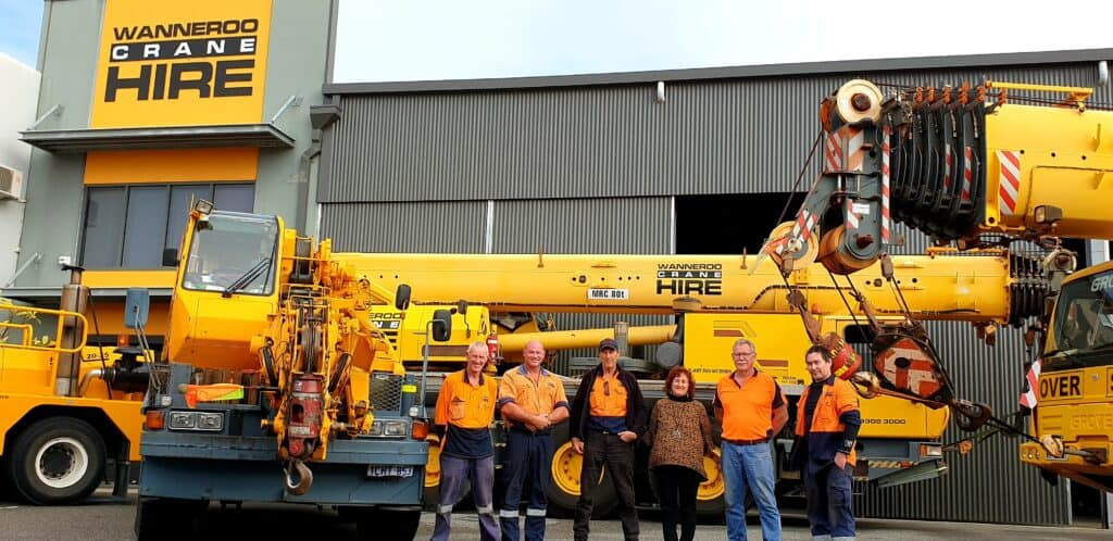 staff posing with cranes in front of their office